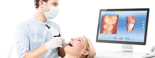 Dentist using CEREC system to view patient's smile