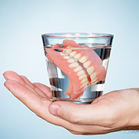 Hand holding glass with dentures in water
