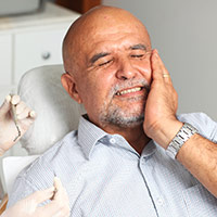Older patient grimacing in dental chair