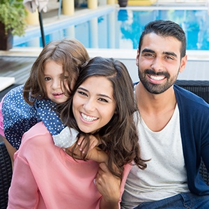 family smiling beside pool