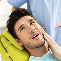Young man in dental chair holding face