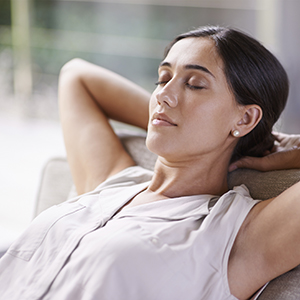 Woman relaxing with hands behind head