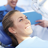 Young woman in dental chair smiling