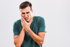 Young man holding cheek in pain need Arlington emergency dentist