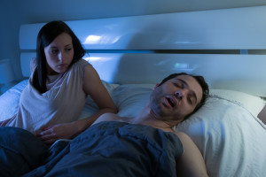 Woman staring at snoring husband in bed