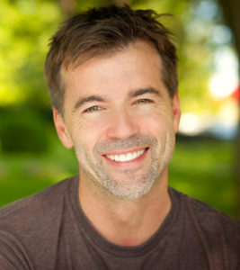 Older man with perfect smile after restoration with CEREC in Arlington