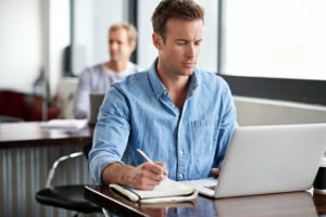 man looking at insurance policy on laptop