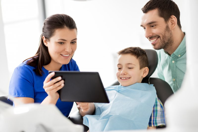 a dentist showing a boy and his father an image on a tablet