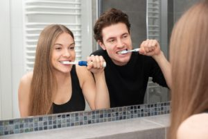 young couple brushing teeth at home in front of mirror