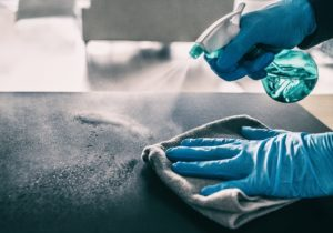 Gloved hands using disinfectant to clean dental office waiting room