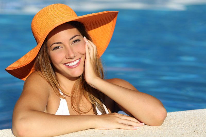 Woman with orange hat smiling in the pool